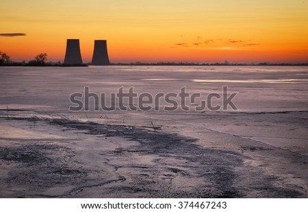 Winter landscape with frozen lake, sunset sky and power plant. - stock photo
