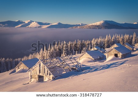 Winter landscape with old wooden houses in the mountains. Sunny morning. The village of shepherds - stock photo