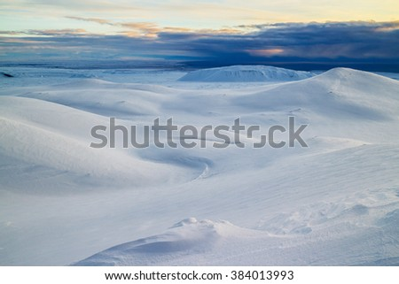 Winter landscape with snow covered mountains in Iceland, dramatic skies in the background. - stock photo