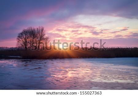 Winter landscape with sun and frozen river. Sunrise. - stock photo
