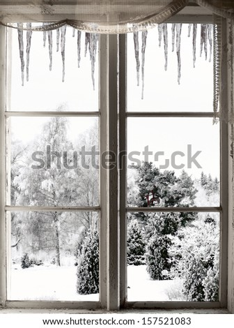 Winter landscape with trees, viewed through old window with icicles - stock photo