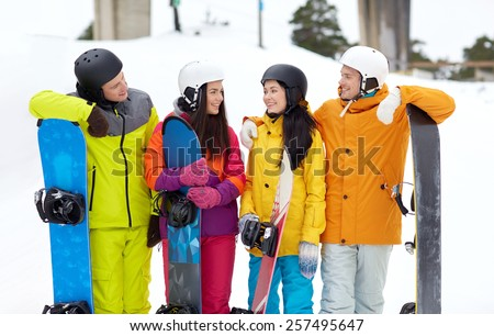 winter, leisure, extreme sport, friendship and people concept - happy friends in helmets with snowboards talking - stock photo