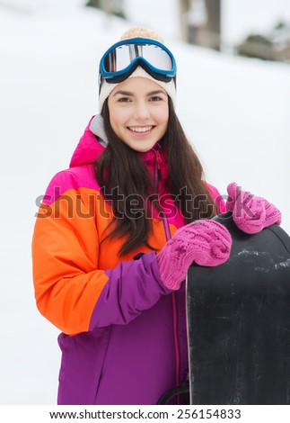 winter, leisure, sport and people concept - happy young woman in ski goggles with snowboard outdoors - stock photo