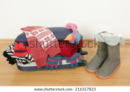Winter luggage. Suitcase full of wither clothes.Packing the suitcase for Christmas vacation. Full luggage and bag with clothes and accessories. - stock photo