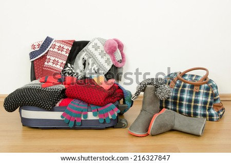 Winter luggage. Suitcase full of wither clothes. Packing the suitcase for Christmas vacation. Full luggage and bag with clothes and accessories. - stock photo