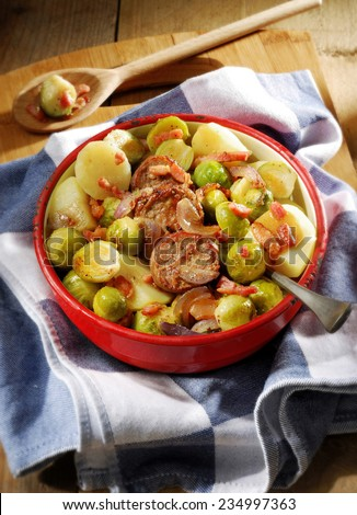 Winter meal. Seasonal fare of potatoes, Brussels sprouts and sausage slices garnished with onion and bacon in rustic enamel serving dish.  - stock photo