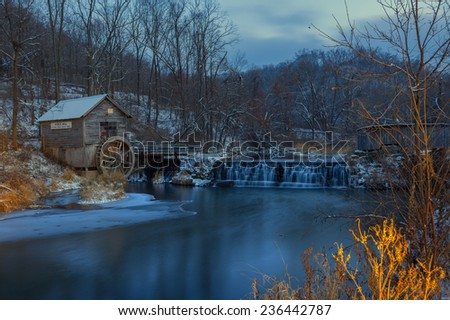 WInter Mill surrounds by snowy covered woods - stock photo