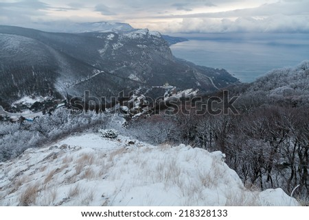Winter misty landscape with mountains and forest. - stock photo