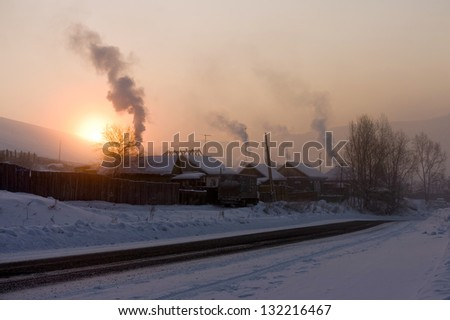 Winter morning in a roadside village, smoke from the chimneys in the sky. - stock photo