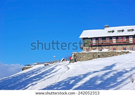 Winter mountain chalet and the blue sky behind - stock photo