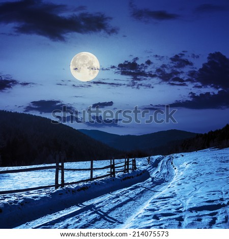 winter mountain landscape. winding road that leads into the pine forest covered with snow. wooden fence stands near the road at night in full moon light - stock photo