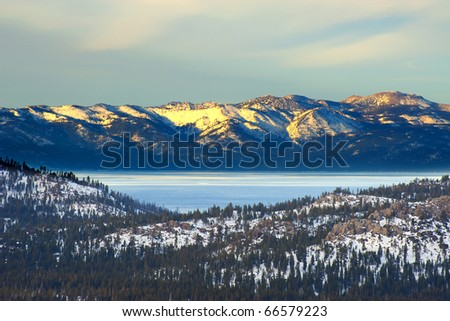 Winter mountain with lake in the trees in the foreground at Lake Tahoe, California - stock photo