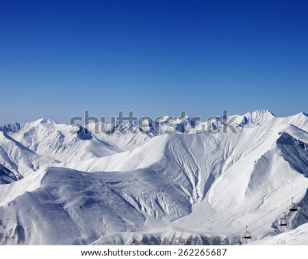 Winter mountains and chair-lift at nice day. Caucasus Mountains, Georgia. Ski resort Gudauri. - stock photo