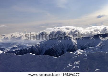 Winter mountains at evening. Caucasus Mountains, Georgia, view from ski resort Gudauri. - stock photo