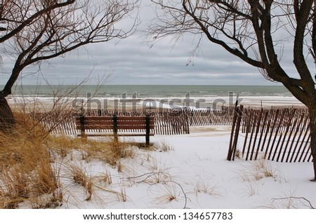 Winter on the Lakes. Park bench framed by bare tree branches on a winter beach. Port Crescent State Park. Port Austin, Michigan. - stock photo