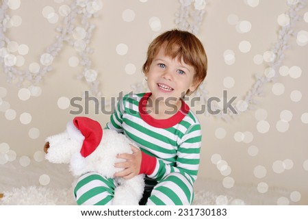 Winter or Christmas Holidays: laughing, smiling, happy child, kid in red and green striped pj pajamas on wood sled in fake snow, snowflakes - stock photo