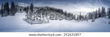 """Winter panorama with a snowy forest and a small chapel, called """"Pestkapelle"""", build in 1639 as a thank you for the end of a plague. Landscape caught in the Austrian alpine forests, Ehrwald resort.  - stock photo"""
