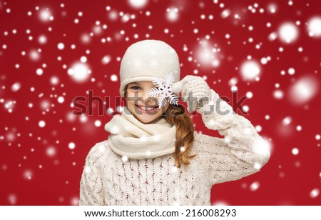 winter, people, happiness concept - smiling girl in hat, muffler and gloves with big snowflake - stock photo