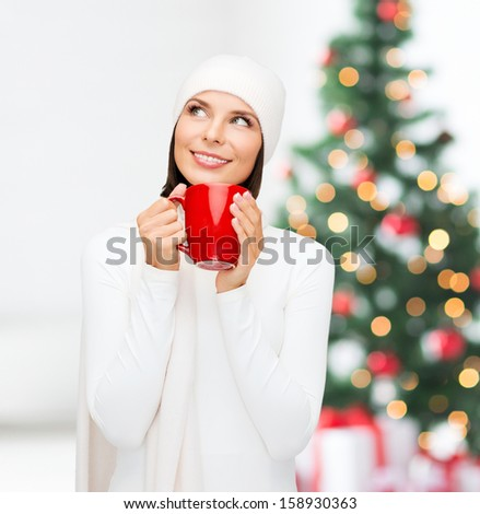 winter, people, happiness, drink and food concept - woman in hat with red tea or coffee mug - stock photo