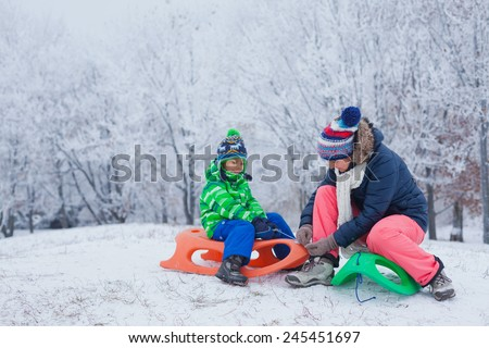 Winter, play, fun - Mother and her cute little son having fun with sled in winter park - stock photo