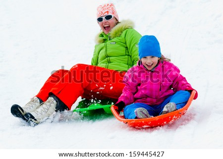 Winter playing, fun, snow and family sledding at winter time - stock photo