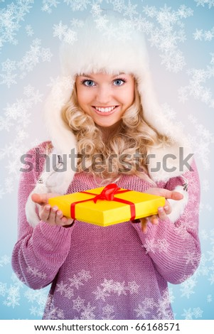 winter portrait of a smiling woman with a gift in her hands and snowflakes - stock photo
