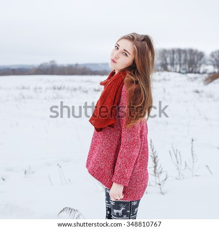 winter portrait of beautiful cute young serious thoughtful girl with red sweater and scarf with black and white trousers and mittens standing on natural background in field outdoor - stock photo