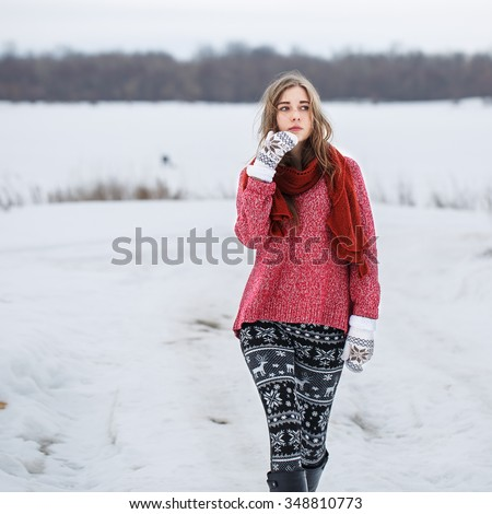 winter portrait of beautiful cute young serious thoughtful girl with red sweater and scarf with black and white trousers and mittens walking on natural background in field outdoor - stock photo
