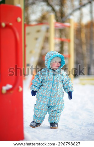Winter portrait of beautiful toddler boy on playground - stock photo