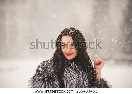 winter portrait of Beauty girl with snow - with film effect with small grain - stock photo