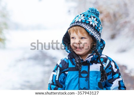 Winter portrait of funny kid boy in colorful clothes, outdoors during snowfall. Active outoors leisure with children in winter on cold snowy days. Happy toddler child having fun with snow in forest - stock photo