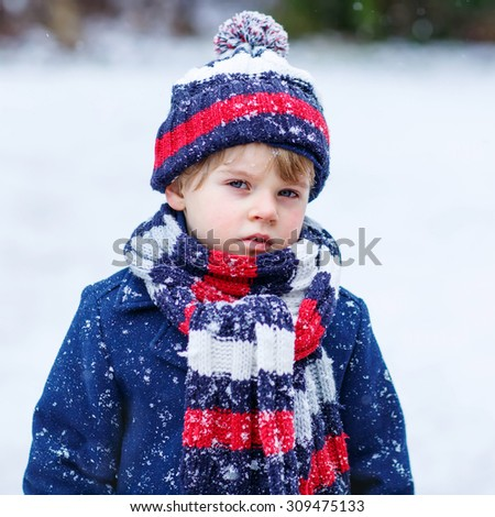 Winter portrait of kid boy in colorful winter clothes, outdoors during snowfall. Active outdoors leisure with children in winter on cold snowy days - stock photo