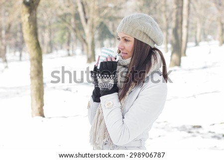 Winter Portrait of Lovely Female Enjoying drinking cup of hot tea outdoor.Beautiful woman relaxing in the park. - stock photo