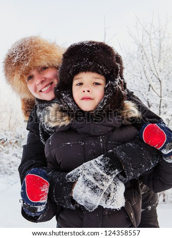 Winter portrait of mother and son - stock photo