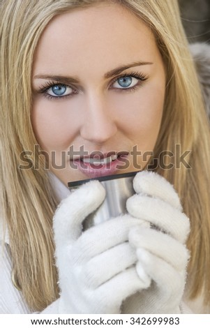 Winter portrait of naturally beautiful woman in her twenties with blond hair and blue eyes wearing gloves and drinking warm drink - stock photo