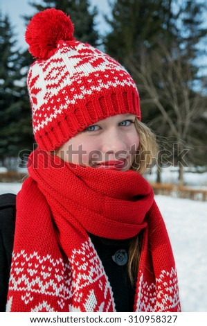 Winter portrait of the beautiful girl in red woolen cap and scarf - stock photo