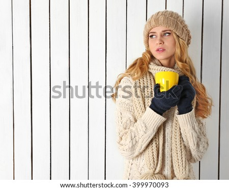 Winter portrait of young beautiful blond woman in her knitted warm clothing, with cup of hot drink - stock photo