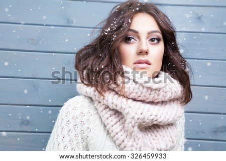 Winter portrait of young beautiful brunette woman wearing knitted snood covered in snow. Snowing winter beauty fashion concept. - stock photo