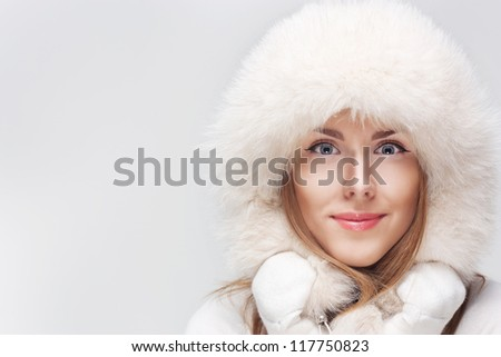Winter portrait of young smiling woman in white fur hat and white mittens on a light background - stock photo