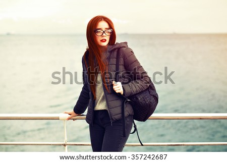 Winter portrait of young stunning traveler woman, posing near sea at lonely beach, red lips, neon hat, warm coat, backpack, street style outfit, rainy windy cold weather, hipster style.vintage colors. - stock photo
