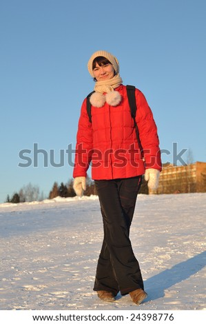 Winter portrait of young woman posing on hill and smiling - stock photo