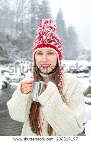 winter portrait woman drinking hot tea over amazing snowy landscape. focus on face - stock photo