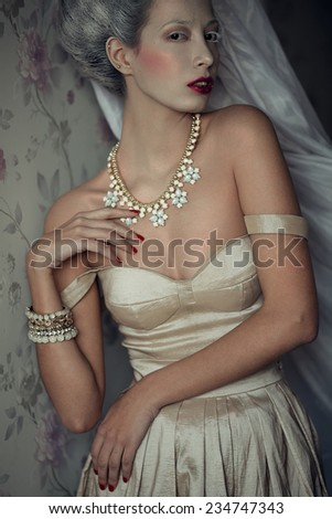 Winter queen concept. Vintage portrait of beautiful young woman with gray hair in beige retro dress. Luxurious golden accessories. Arty make-up, perfect hairdo. Rococo style. Studio shot - stock photo