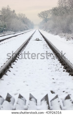 winter railroad track diminishing into a distant hazy sunset (landscape crop also available) - stock photo