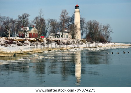 Winter reflections at Point Aux Barques Lighthouse. Geese in the cold water of Lake Huron, Port Hope, Michigan USA - stock photo