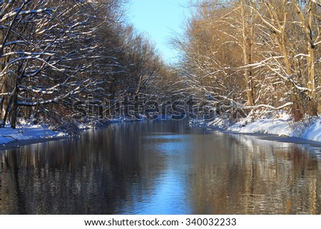 Winter River - A snow covered forest with water reflections. - stock photo