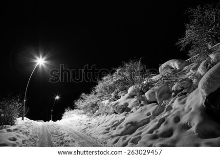 Winter road at night, illuminated by lanterns - stock photo