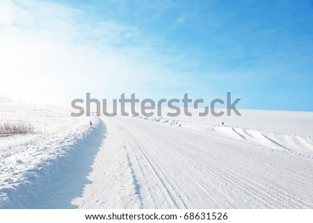 Winter road under blue sky. - stock photo