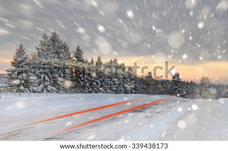 Winter road with snow showers. Taken with a slow shutter speed, you see the lights of a passing car. Copy space. Winter background. - stock photo