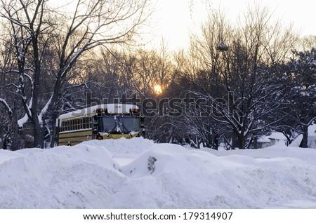 Winter routine: School bus parked on snowy neighborhood street after sunrise, northern Illinois, USA - stock photo